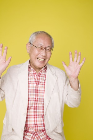 wimp: Old man has been surprised by raising both hands Stock Photo
