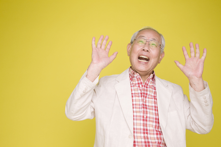 senior men: Old man has been surprised by raising both hands Stock Photo