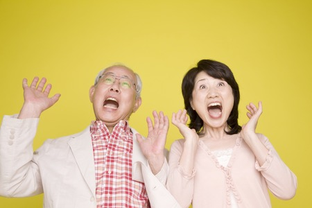 Old couple you surprised by raising both hands Banco de Imagens