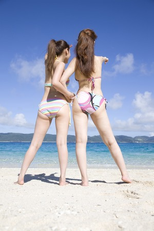 back shot: Back shot of two women overlooking the sea from the beach Stock Photo