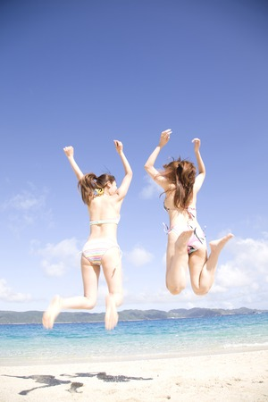 back shot: Back shot of two women wearing a bathing suit to jump on the beach