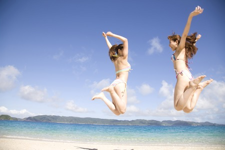 Back shot of two women wearing a bathing suit to jump on the beach