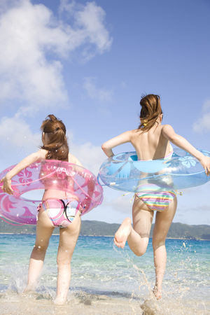 inner tube: 2 women Rear View entering the sea with a inner tube
