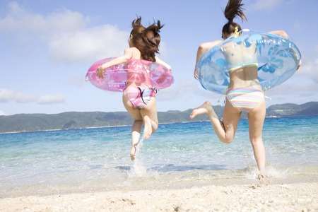 2 women Rear View entering the sea with a inner tube