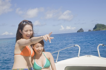 other side of: Two swimsuit women Pointing the other side of the sea ride to the yacht
