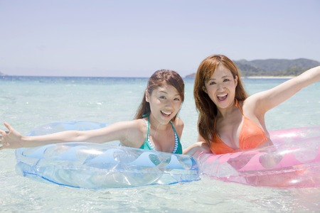 two wheel: Two swimsuit woman riding a wheel floating in the sea