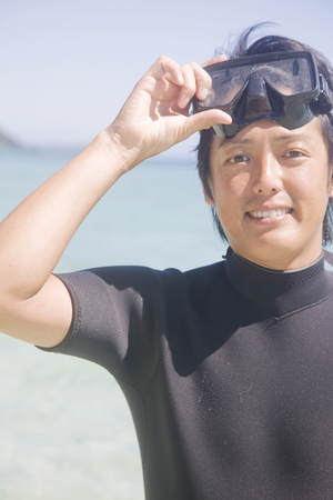 wet suit: Man wearing a wet suit to put the by standing on beach snorkel Stock Photo