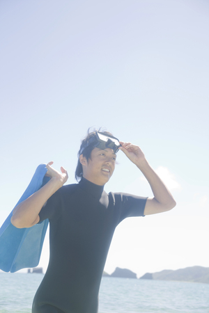 wet suit: Man wearing a wet suit that start with a fin to the beach Stock Photo