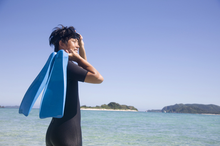wet suit: Man wearing a wet suit that look up at the sun in the beach has a fin