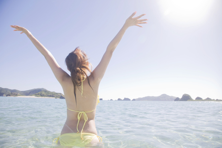 enters: Rear View of swimsuit women to extend enters the sea Stock Photo