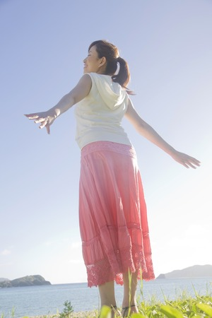 bathed: Rear of women bathed in the light of the sun open arms at the beach Stock Photo