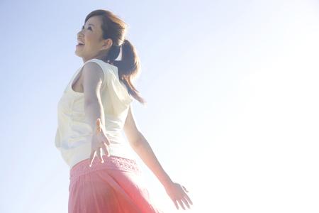 女性は太陽の光にさらされ、青空の下で腕を開く 写真素材