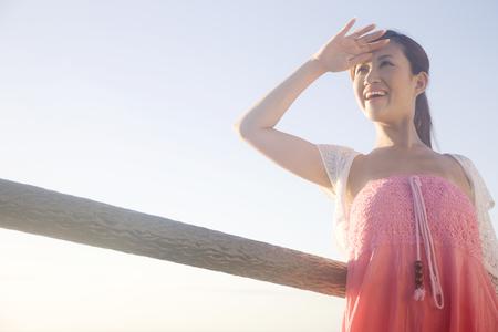 Vrouwen die naar de hemel kijken terwijl je je hand aan de kust houdt Stockfoto
