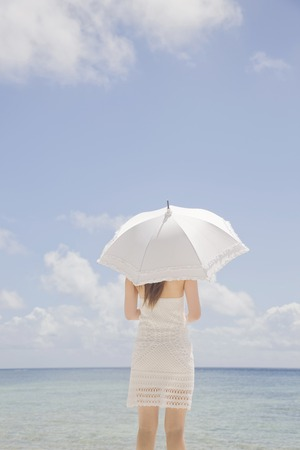back shot: Back shot of a woman standing on the beach with parasols