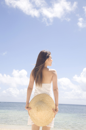 back shot: Back shot of a woman standing on the beach with a straw hat