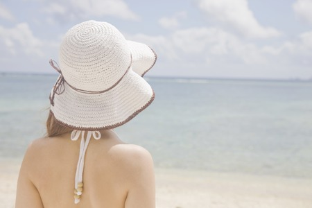 back shot: Back shot of a woman wearing a hat overlooking the sea