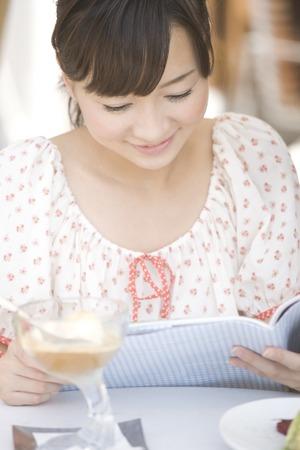seres vivos: Las mujeres que leen la revista en un caf� al aire libre Foto de archivo