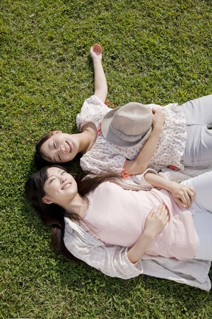 Two women lie down on the grass Stock Photo