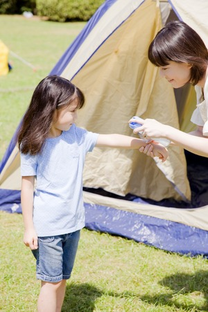 Mother of applying insect repellent to daughter
