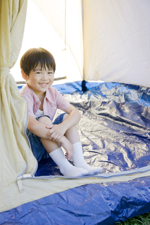 gratification: Boy looking out from inside the tent
