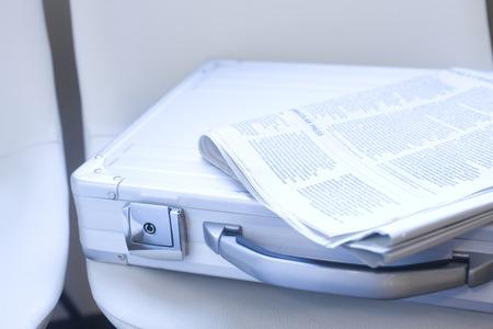 スーツケースと椅子に配置されている新聞 写真素材