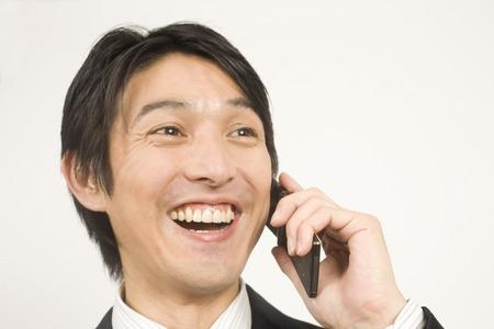 通信: ビジネスマンが携帯電話で話しています。