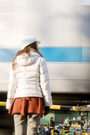 railroad crossing: Rear View of a woman standing on the railroad crossing
