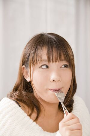 gratification: Woman eating cake Stock Photo