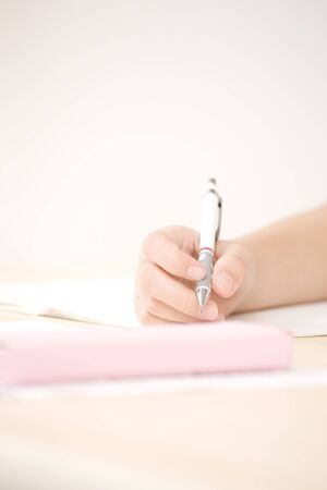 writing utensil: Hand of the girl to study in the School Stock Photo