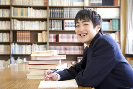 uniforme escolar: Estudiantes de secundaria de los hombres para estudiar en la biblioteca