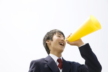 Mens junior high school students shout in megaphone Stock Photo