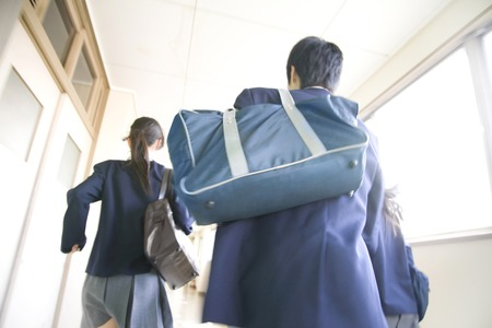 Male and female junior high school students run down the hallway photo