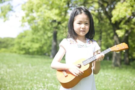 seres vivos: Chica tocando el ukelele Foto de archivo