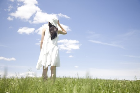 Back view of woman standing in grassland Stock Photo