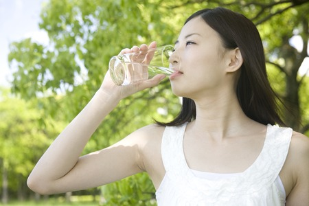 water plant: Woman drinking water Stock Photo
