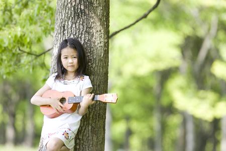 livelihood: Girl playing the ukulele Stock Photo