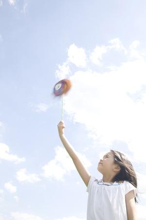 seres vivos: Ni�a jugando con molino de viento Foto de archivo