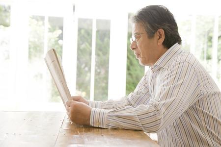 information age: Senior man reading newspaper