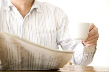 一杯のコーヒーと年配の男性の手