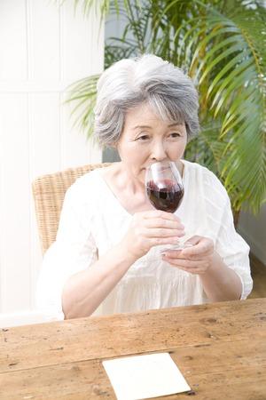 赤ワインを飲む年長女性 写真素材
