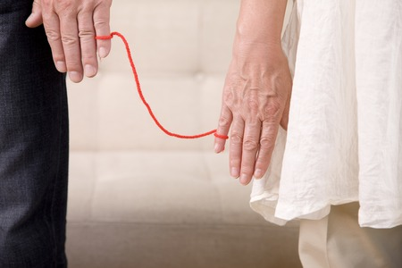 little finger: Hand of an elderly couple that was connected the little finger with a red wool