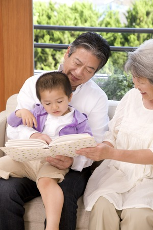 play date: Elderly couple reading a book grandson Stock Photo