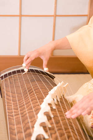 musical instrument parts: Woman playing the harp in hand