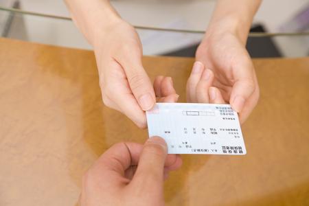 Ruku od mužského pacienta zubních hygienistů, aby obdržel pojistnou kartu