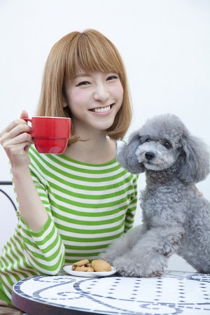 Women with a toy poodle and mug