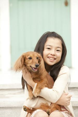 Girl hugging a miniature Dachshund