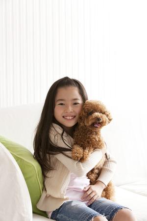 Girl smile hugged toy poodle Foto de archivo