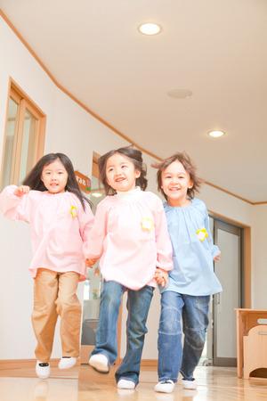 bebes niñas: Kindergarten tres personas corriendo por el pasillo Foto de archivo