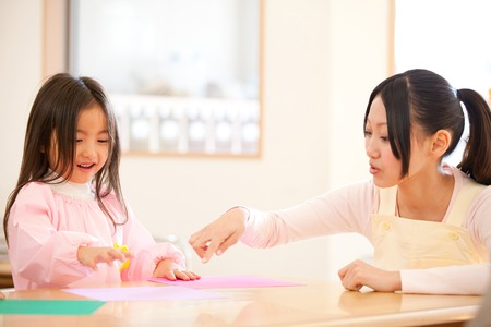 kindy: Kindergarten girls and kindergarten teachers folding origami Stock Photo