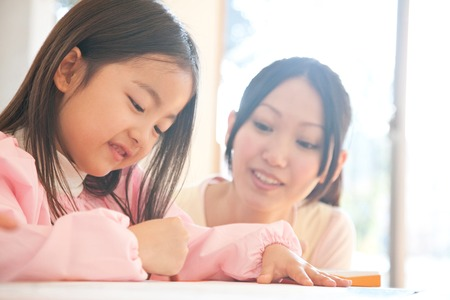 asian toddler: Kindergarten girls enjoy drawing and kindergarten teacher watches